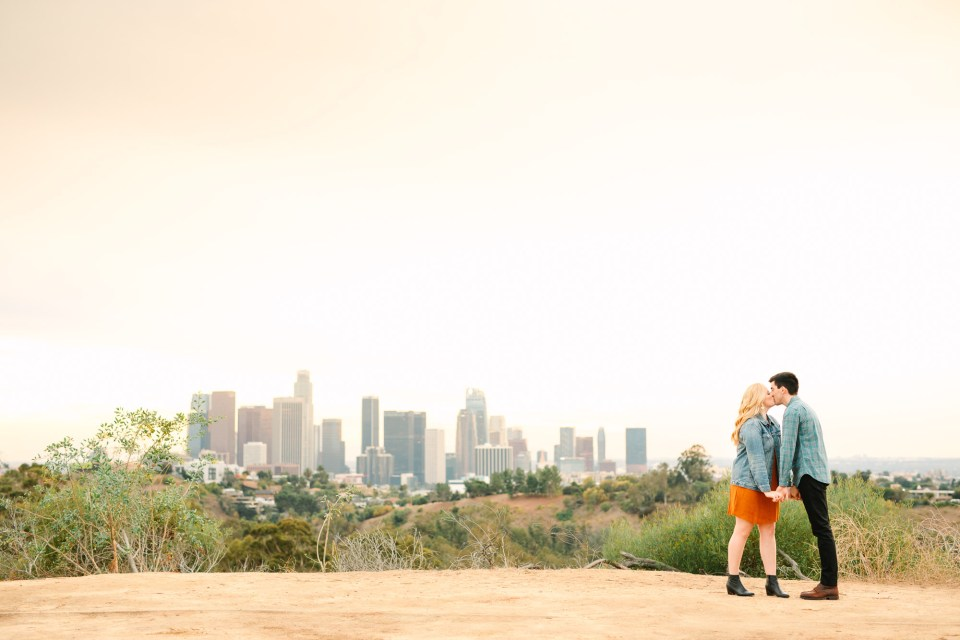 Couple kissing with Los Angeles DTLA skyline Indian Fusion wedding at Fig House Los Angeles by Mary Costa Photography