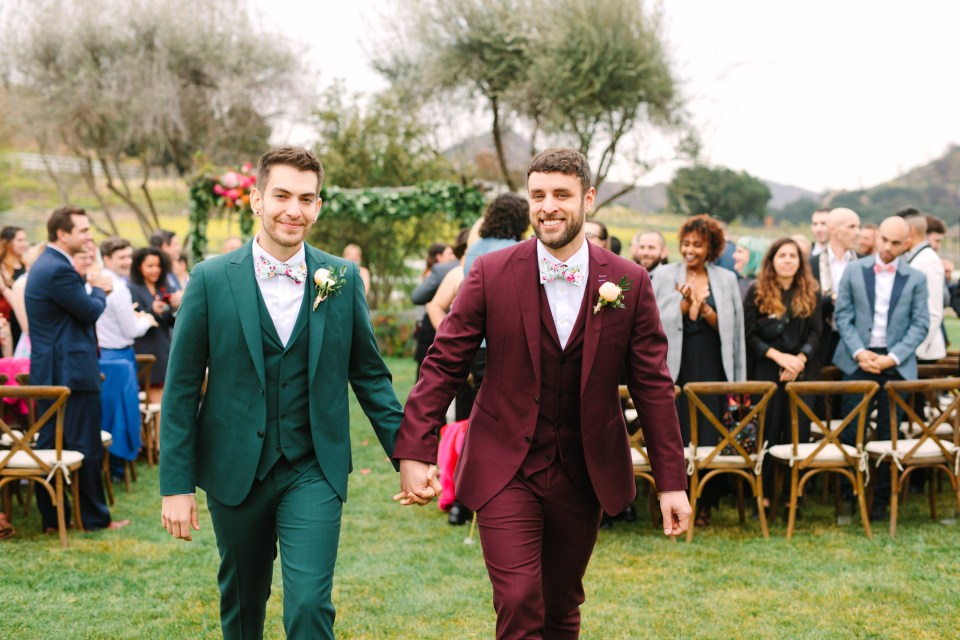 Two grooms leaving wedding ceremony by Mary Costa Photography
