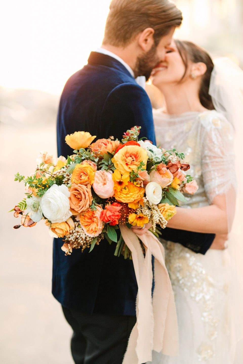 Wedding couple embracing with colorful bouquet www.marycostaweddings.com