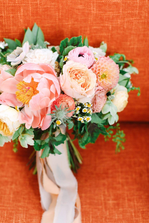 Peony bouquet on orange couch - www.marycostaweddings.com