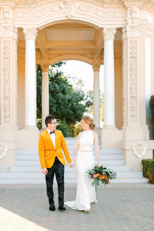 Bride and colorful groom walking in San Diego's Balboa Park - www.marycostaweddings.com