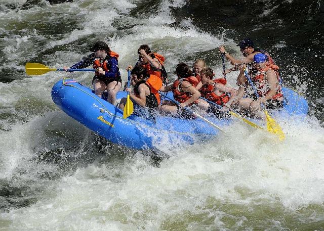 Grupp som paddlar i kraftiga vågor, symboliserar teamarbete