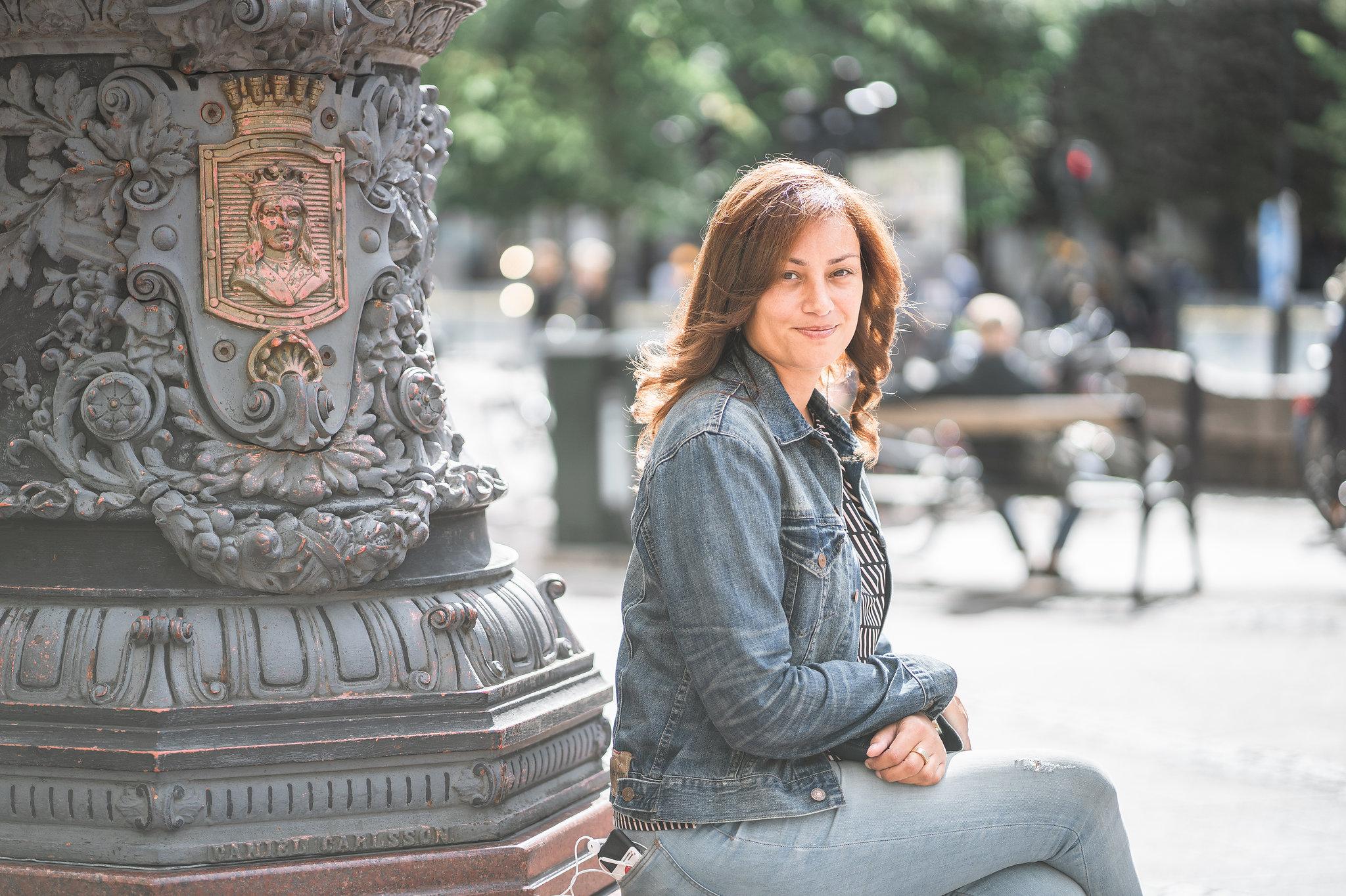 Maryem Nasri, projektledare. Sitter på Stureplan i solen. Hon har på sig jeans och jeansjacka.
