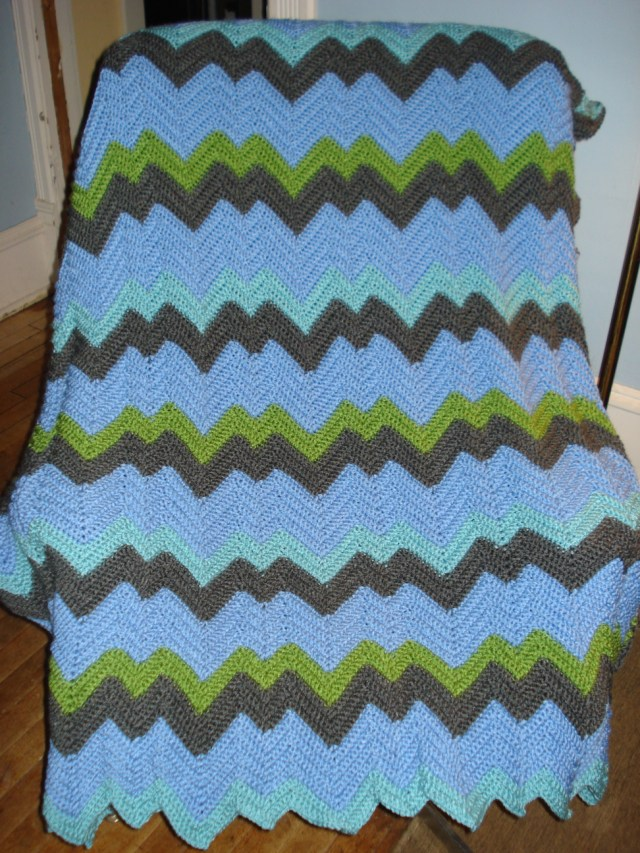 Zigzag crocheted afghan with light blue, light green, vibrant green, and gray zigzags by Mary Warner, 2014.