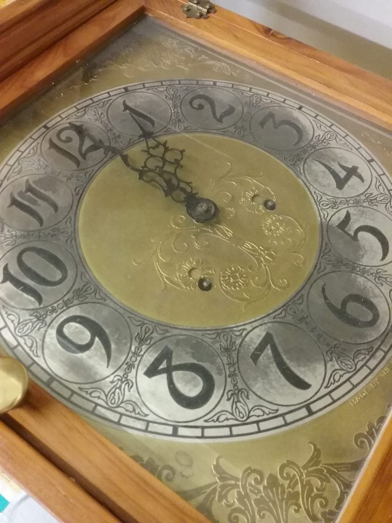 Clock with fancy numbers, face, and hands lying on its back, 2018.