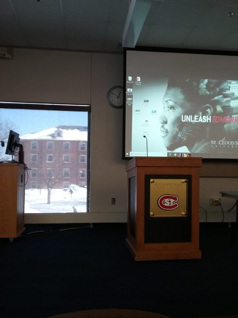 Clock peeking from behind screen in Voyageur's North conference room at St. Cloud State University during archaeology conference, February 15, 2019.