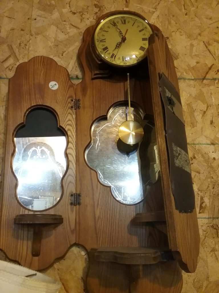Clock with folding wood base that appears to be falling apart, 2019.