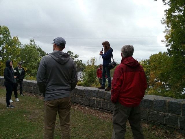 Sue Granger of Gemini Research giving us some of the history of the granite wall she is standing on, Riverside Park, St. Cloud, MN, September 13, 2019.