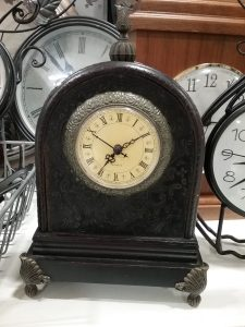 Black mantle clock with white face, black numbers and hands, several clocks behind, 2019.