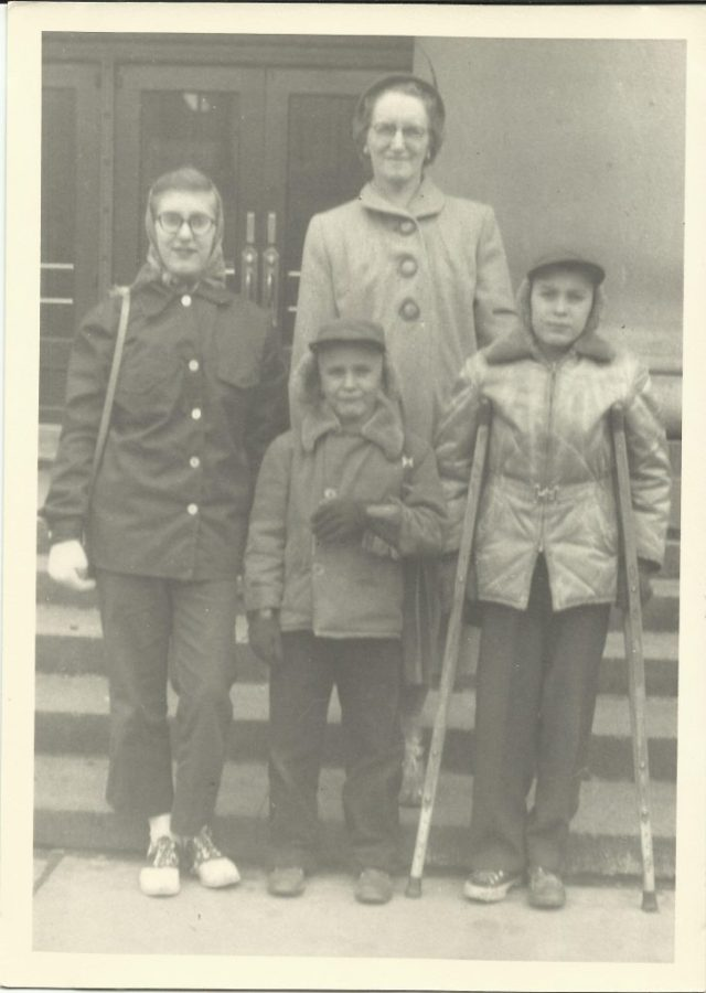Judy, Dick, and John Rasmussen with their Aunt Ellen. John, my father, is the one with crutches, which he needed because of the polio he suffered, March 1955.