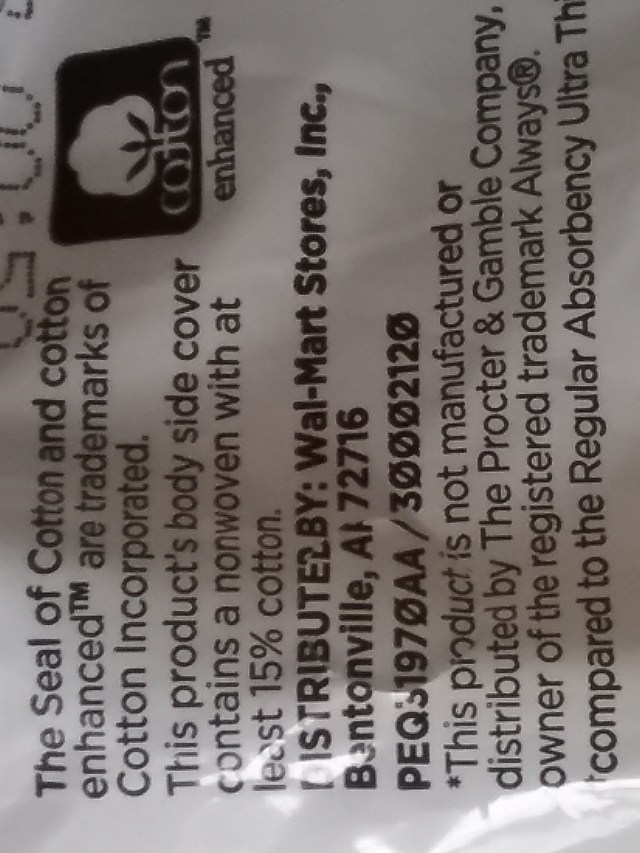 """Close-up of packaging from Equate Ultra Thin Pads from Walmart. Note the """"Cotton Enhanced"""" symbol and that the product promises that the """"body side cover contains a nonwoven with at least 15% cotton."""" Don't get carried away with the cotton, Equate! November 15, 2020."""