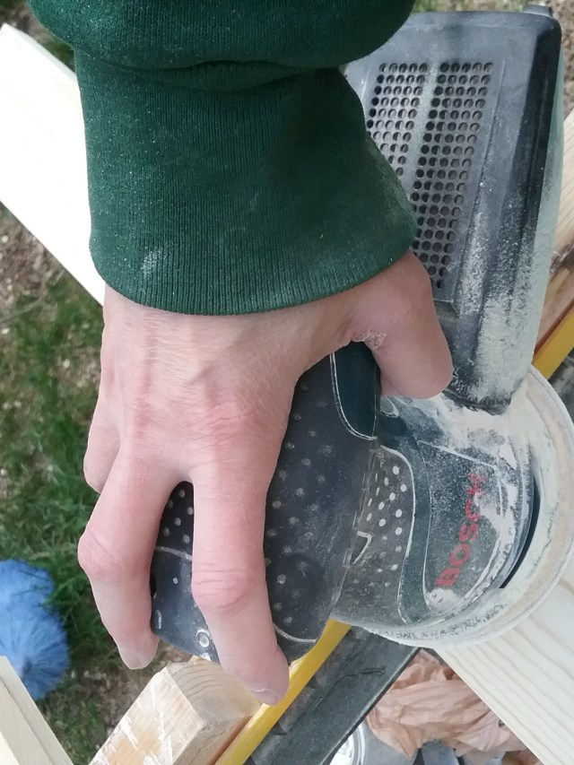 Me, using a random orbital sander to sand trim for our house, May 30, 2021. Note that my hand is a little small to properly hold the sander, which has obviously been designed with bigger hands in mind.