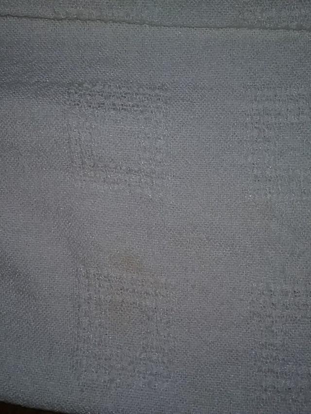 Closeup image of lace squares embedded in handwoven fabric of Eldest Son's white baptism gown.