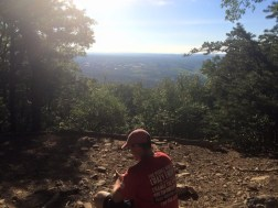 Seamus O'Hara, a Penn State student, takes a break at the lookout point of the White Trail at Mount Nittany.