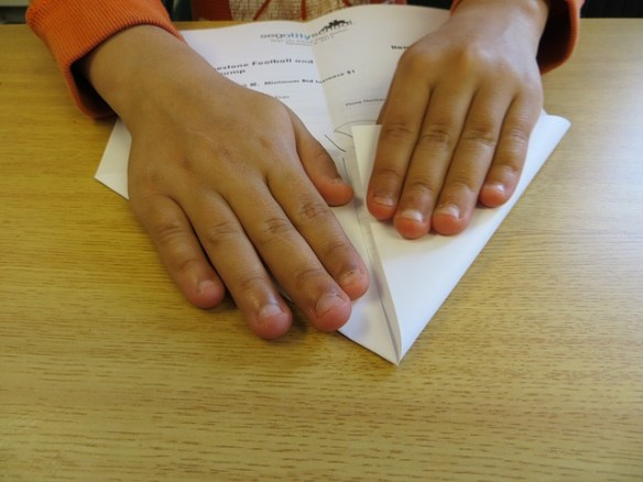 child's hands folding paper airplane