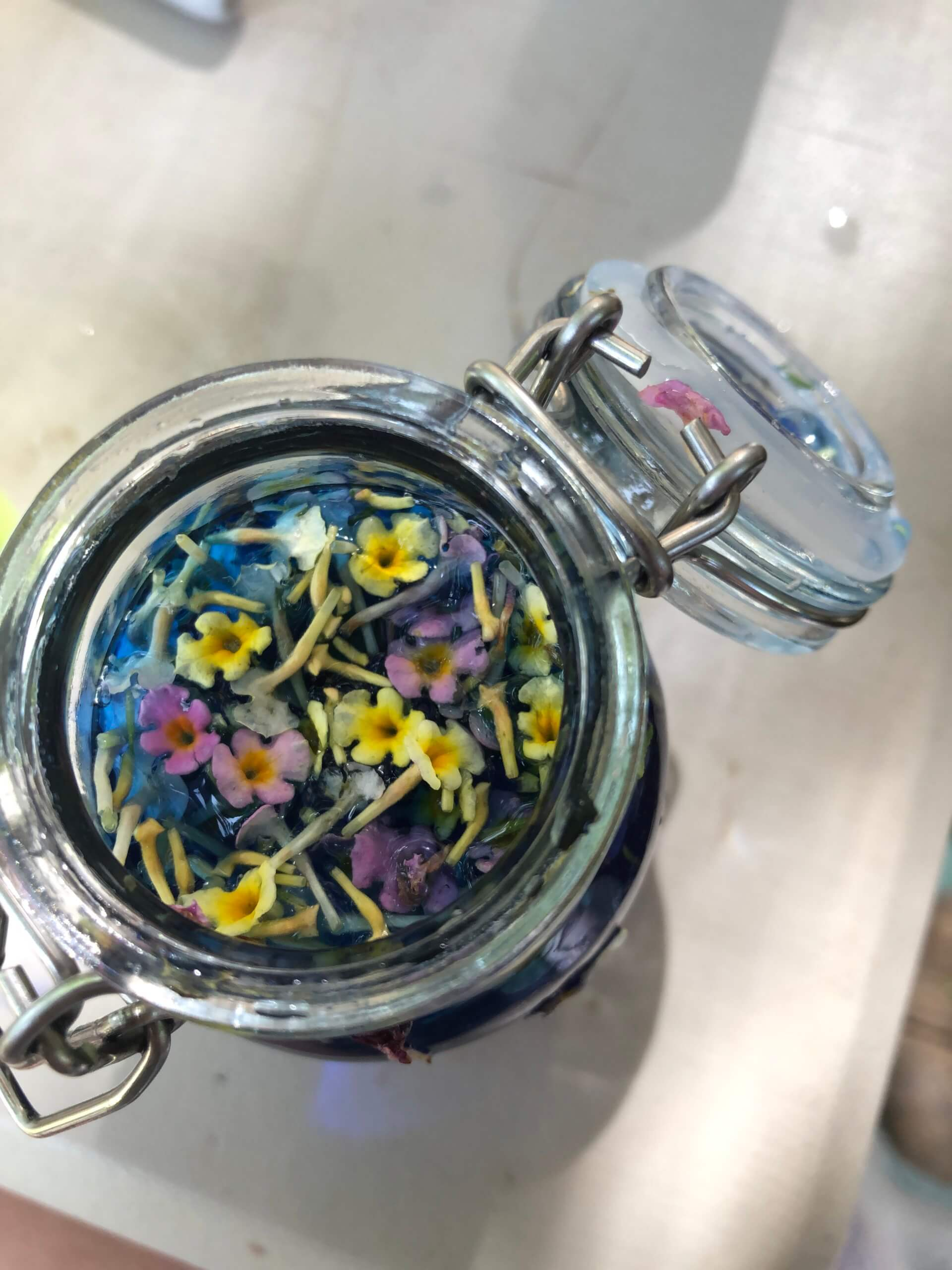 Open jar of blue liquid with colorful flowers