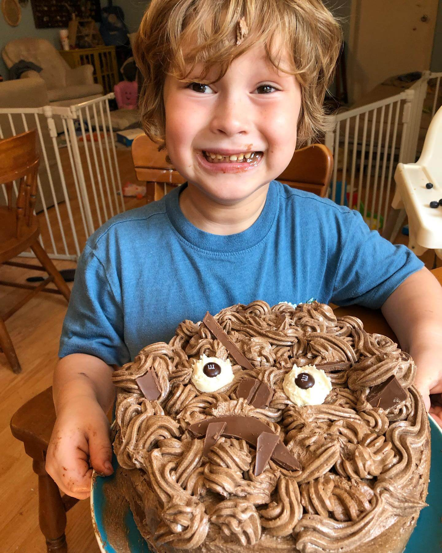 child holding a chocolate frosted cake