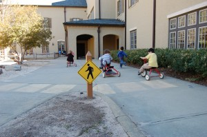 "Play: These Kindergarten ""drivers"" experience both structured and unstructured play as they navigate the rules of the road on their trike bikes."