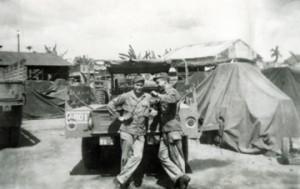 Ivan Schulze & John Schritz leaning on truck in camp