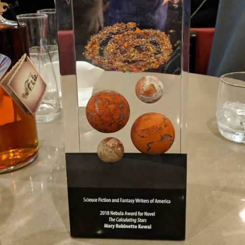 The 2018 Nebula Award for Novel contains reddish stones representing planets and a swirl like a Nebula.