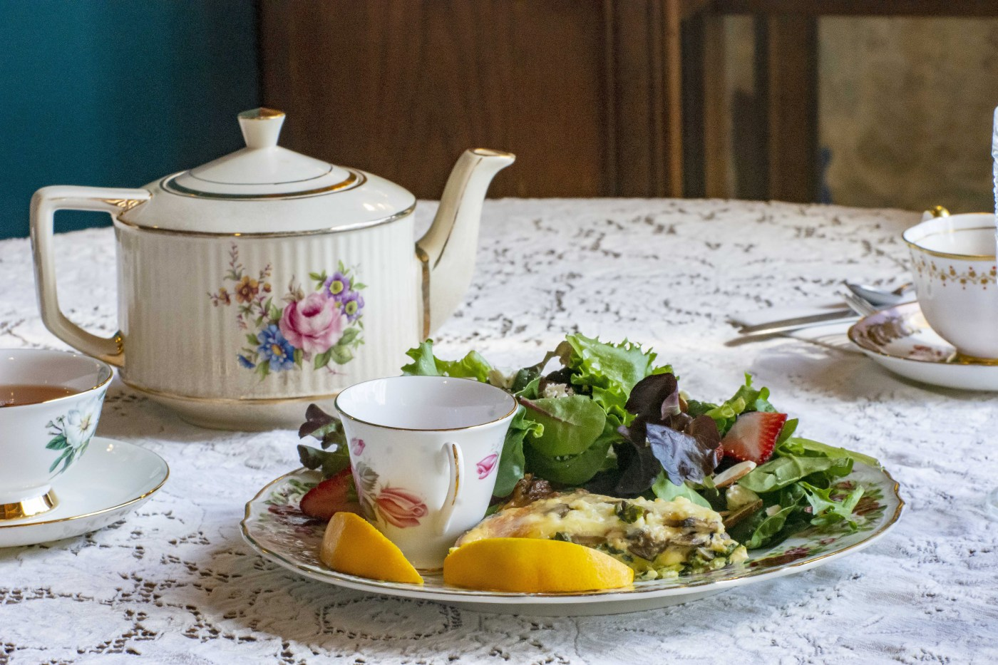 Teapot and cup with plate of food on a lace covered table