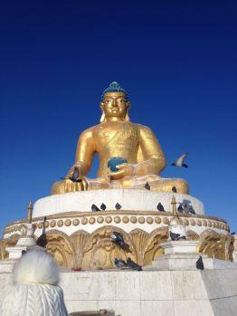Buddha statue against brilliant blue sky.