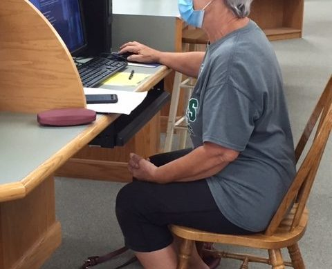 Woman using library computer.
