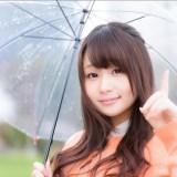 傘をさして左手人差し指をたてる女性