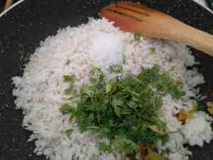 Mixing of poha into the sauteed mixture of onions and potatoes