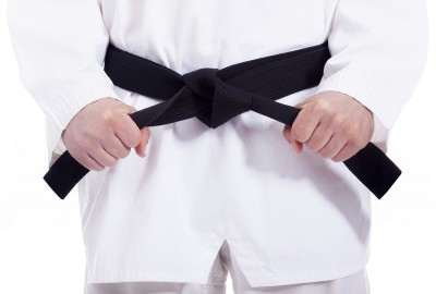 bigstock-Martial-arts-man-tying-his-bla-47307487
