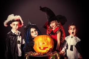 Cheerful children in halloween costumes posing with pumpkin over
