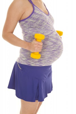 a woman with her weights next to her belly wanting to be a healthy mom.