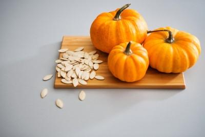 Closeup Of Miniature Pumpkins And Seeds On A Cutting Board