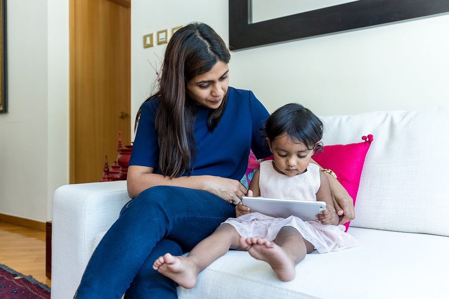 Little girl reading e book on tablet with her mother