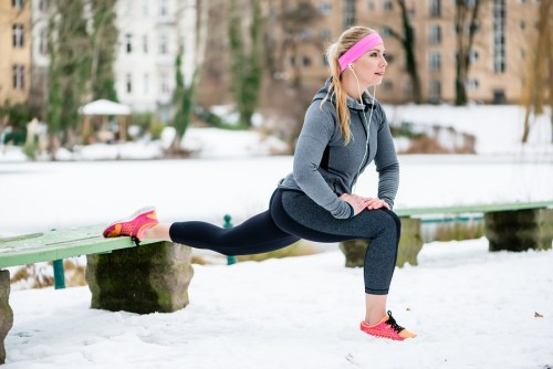 it woman stretching her limbs for sports exercise in winter