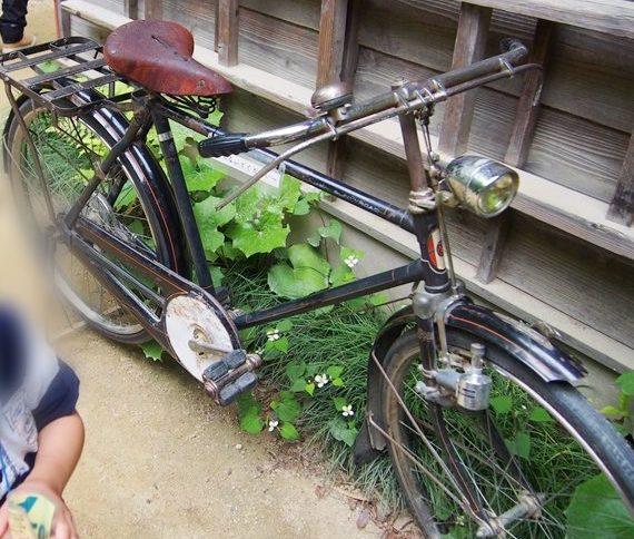サツキとメイの家の壁際にある黒い自転車と隣に子供