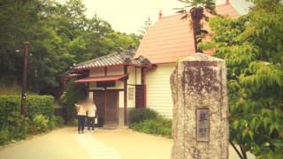 草壁の表札と、奥に赤い屋根の家がある