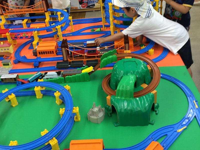 青色のレールと緑の山などプラレールで遊ぶ子供