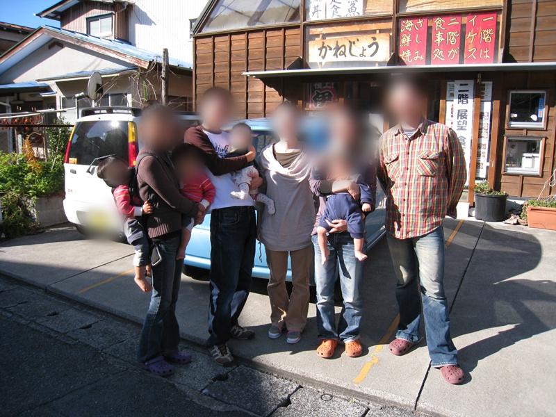 かねじょうの店前に子供を抱っこした大人たちが立っている