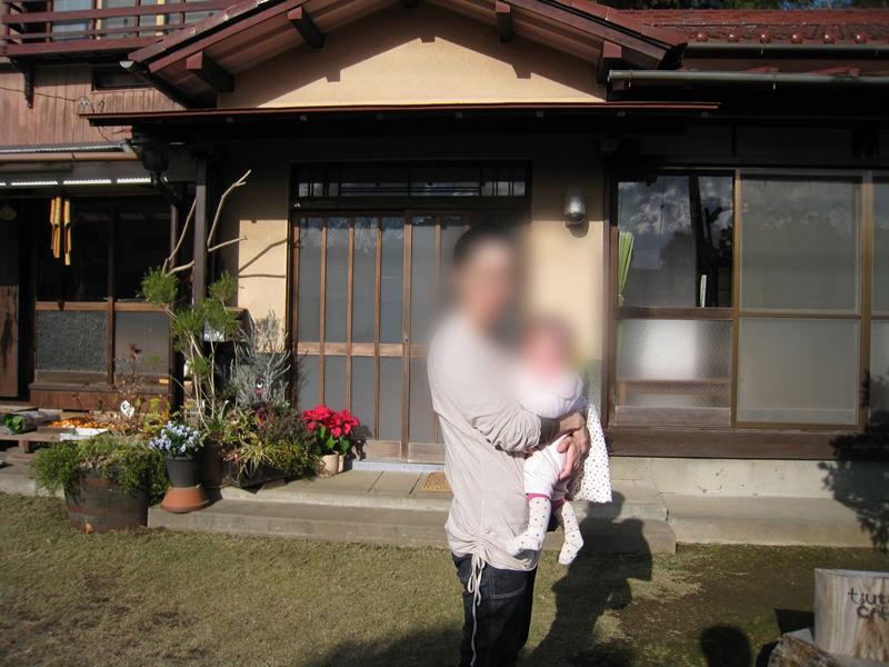 民家の前で赤ちゃんを抱っこしている女性