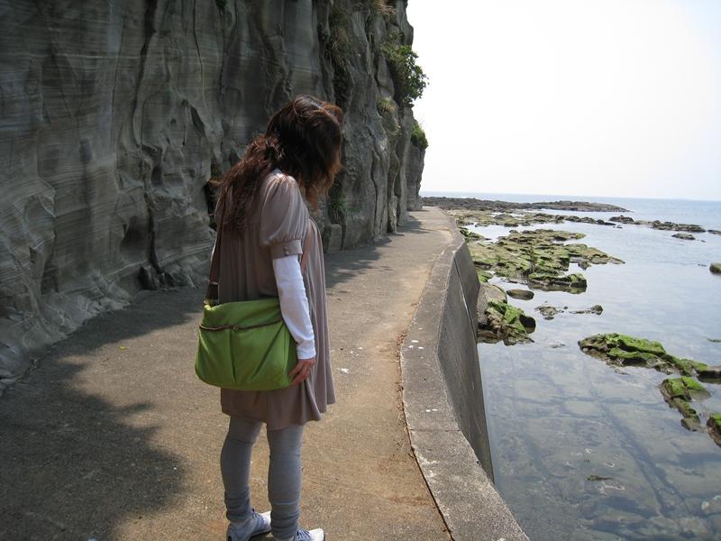 海岸沿いの歩道に立つ女性