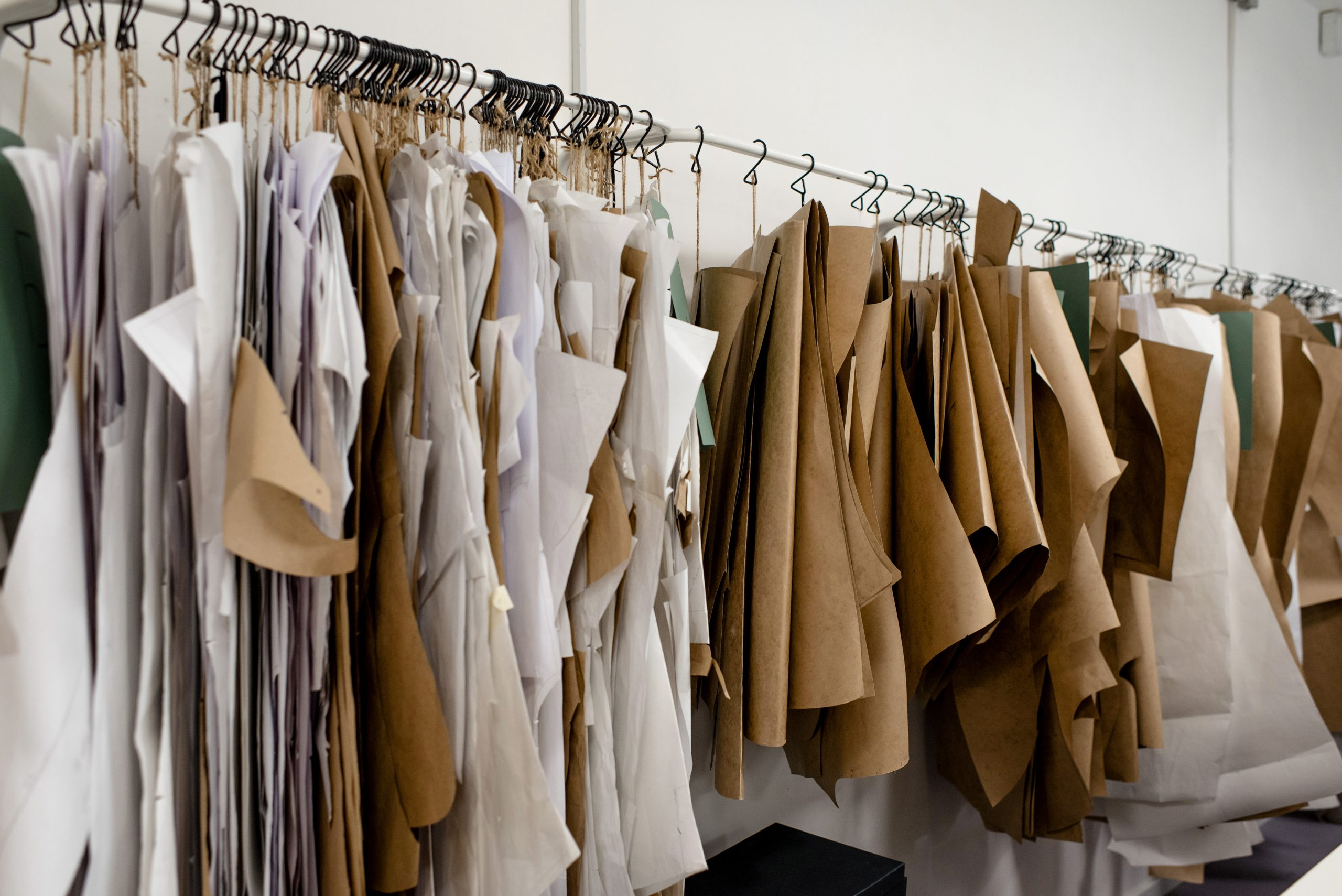 Produsen Pakaian Wanita, Assorted sewing patterns on hangers inside tailor atelier