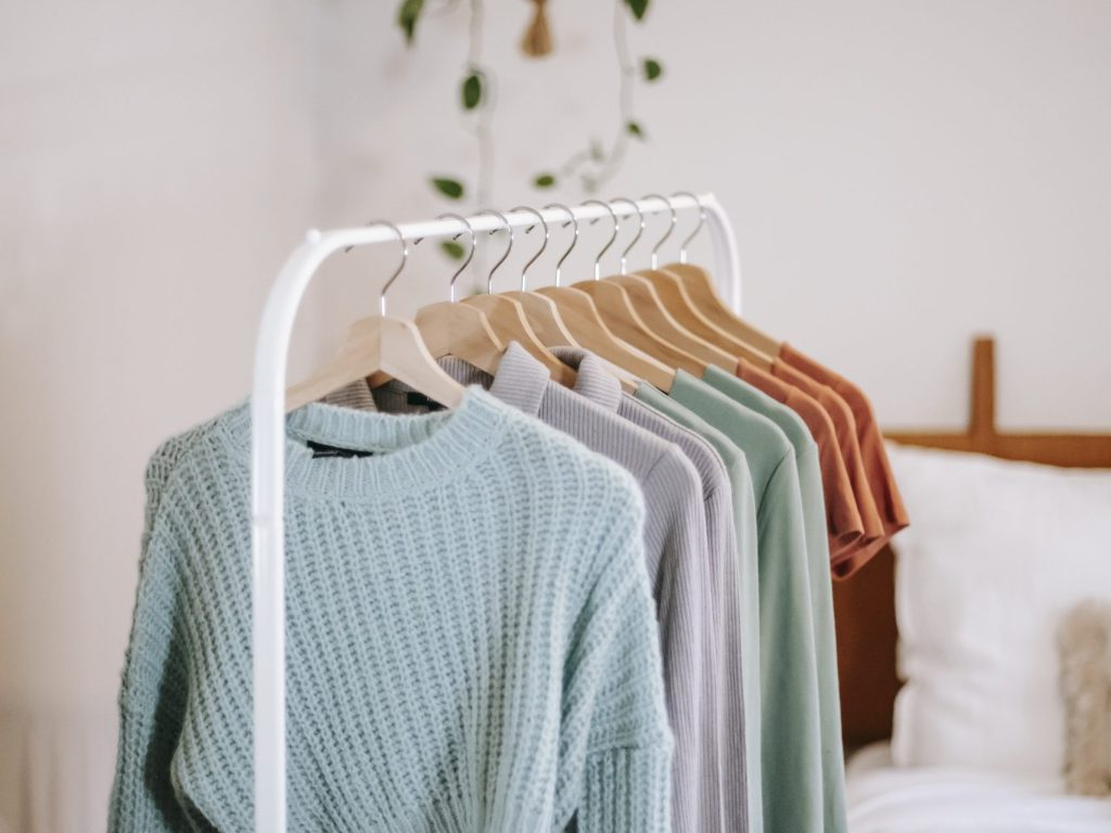 Wardrobe with clothes on hangers near bed at home