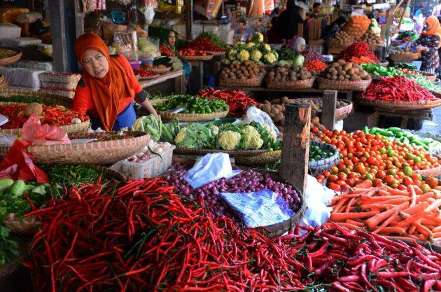 pedagang sayuran melayani pembeli pasar tradisional