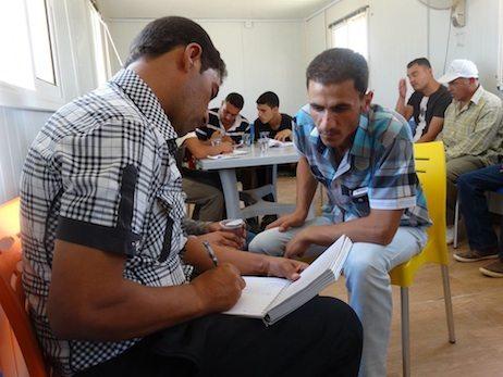 Men writing in the Zaatari refugee camp