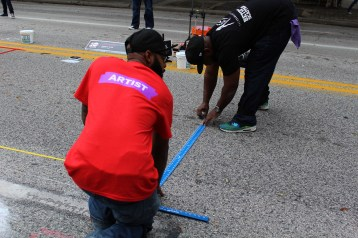 The art of painting streets requires mounds of preparation and precise measurements
