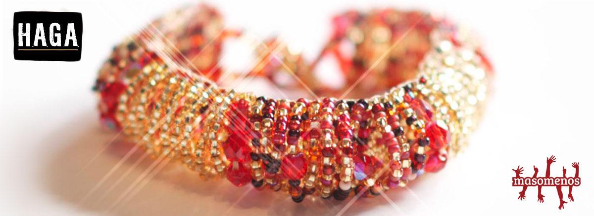 Ett armband i rött och guldfärg, omgivet av loggorna Haga och Masomenos