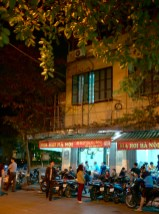 Evening shot of beer hall in Hanoi Vietnam old city with streetlight casting shadows on people outside drinking beer