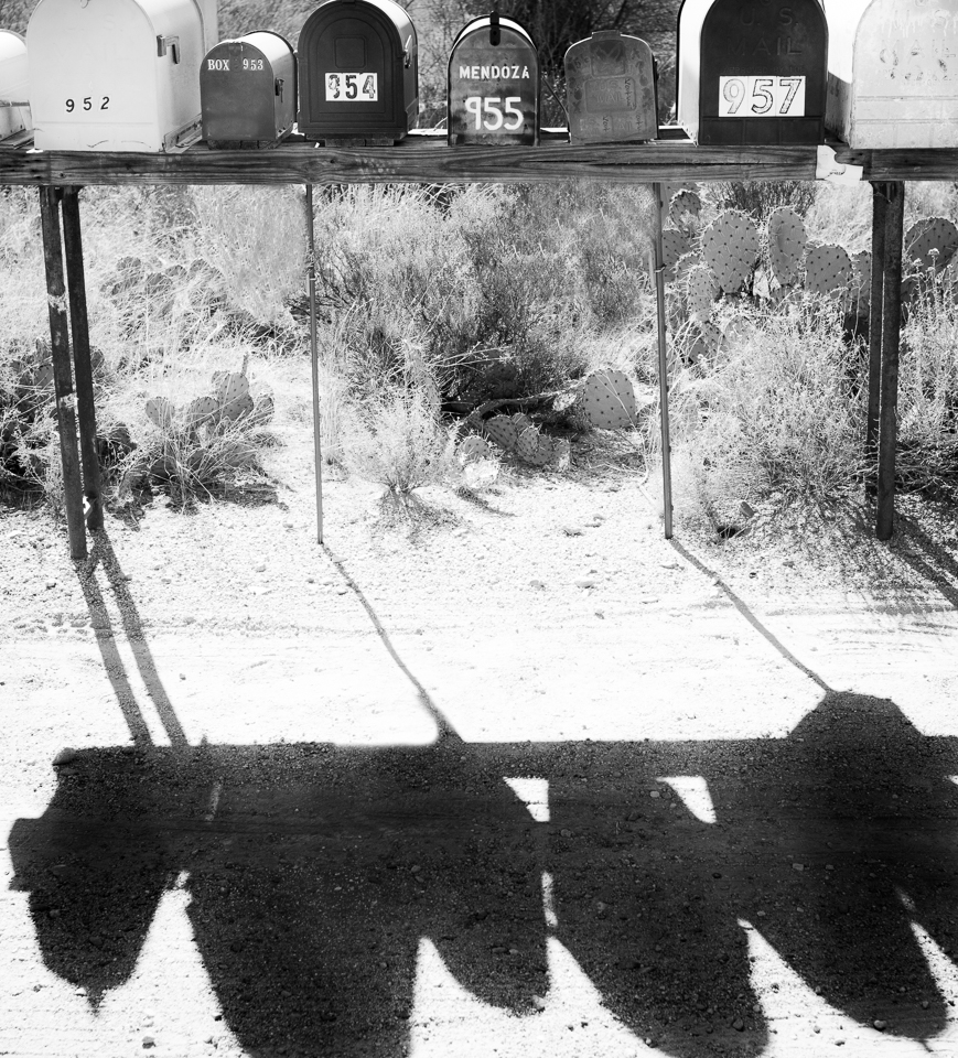 black and white mailboxes on a dusty desert road.