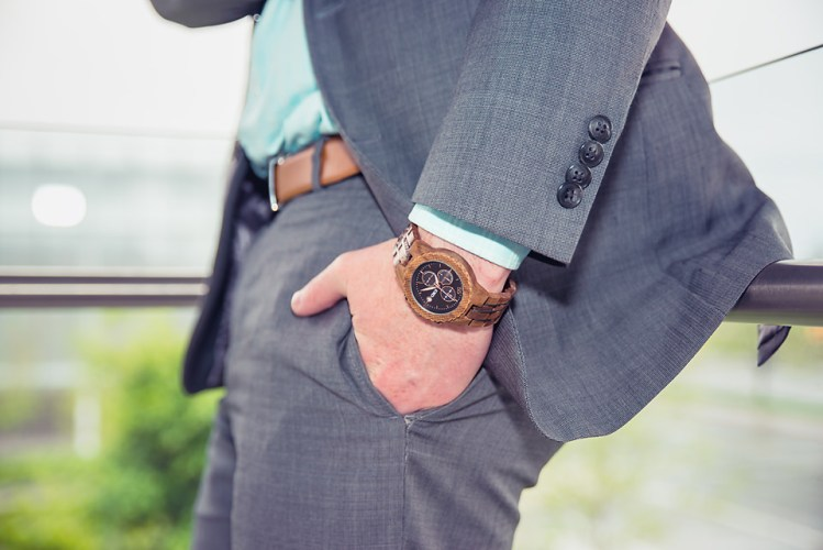 man wearing jord conway series walnut jet black unique wood watch joseph aboud gray suit on glass balcony
